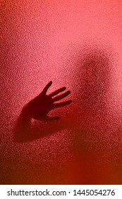 silhouette of a woman through frosted translucent glass, enigmatic gloomy silhouette
