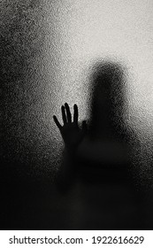 silhouette of a woman through frosted translucent glass, black and white image