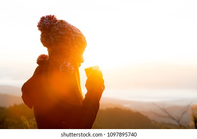 Silhouette woman tourist in winter clothes and fur hat drink a hot coffee over sunrise ,Women's winter in the women's clothing enjoy enjoying tender moments during sunrise,happy life and happy time,