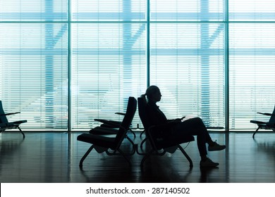 Silhouette of a woman in transit using smarthphone, waiting on airport gate. Horisontal composition. Focus on passanger.