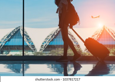 Silhouette woman travel with luggage walking side window at airport terminal international or girl teenager traveling in vacation summer relaxation holding suitcase and backpack