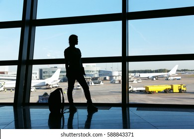 silhouette of a woman traveler with backpack in an airport lounge. business and travel