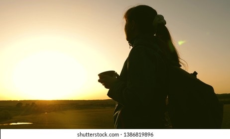 silhouette woman traveler, stands on top of hill drinking coffee in glass from thermos. tourist girl drinks hot tea and looks at sun. Adventurer rest after reaching goal. freedom concept.