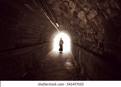 Silhouette of a woman in a tunnel