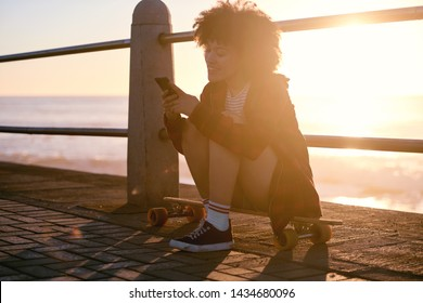 Silhouette of woman using her mobile cell phone by the ocean at sunset