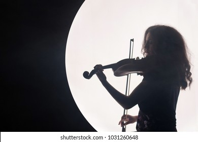 Silhouette of a woman violinist in a white semicircle with smoke on a black background. A concept for music during the full moon. Night background. Copy space.