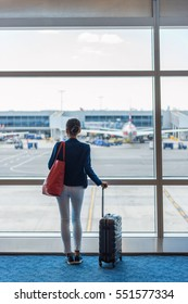 Silhouette of woman waiting at airport terminal for flight boarding. Businesswoman traveling looking through the window at tarmac and planes. Business travel concept.