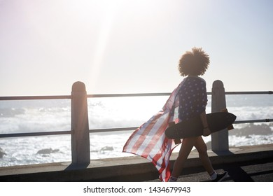 Silhouette of woman walking along the ocean holding long board skateboard and american flag