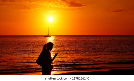 Silhouette of woman walking along sunset beach and looking into a phone on her hand. First Beach Tanjung Aru, Kota Kinabalu, Malaysia