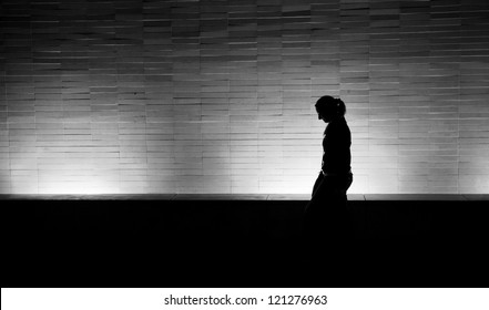 Silhouette of a woman walking at night in the city