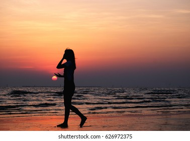 Silhouette Woman walking on the beach at sunset time Beautiful sky