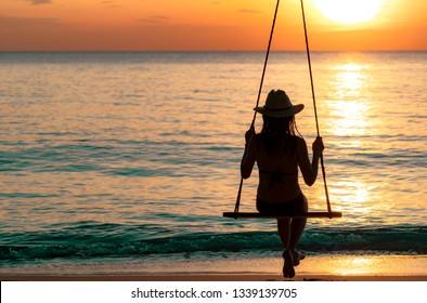 Silhouette woman wear bikini and straw hat swing the swings at the beach on summer vacation at sunset. Girl in swimwear sit on swings and watch beautiful sunset. Summer vibes. Woman travel alone.