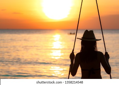 Silhouette woman wear bikini and straw hat swing the swings at the beach on summer vacation at sunset. Enjoying and relaxing girl on holiday. Summer vibes. Woman watching beautiful sunset sky.