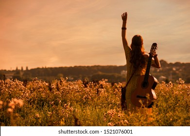silhouette of woman wearing a bohemian style holding a guitar on a field at warm light of sunset