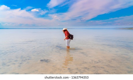 Silhouette of woman wearing red shirt and white hat walking on the famous tourist destination Salt Lake (Turkish: Tuz Golu ) is the second largest lake in Turkey.