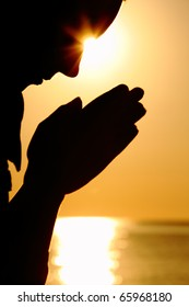 Silhouette of woman which sits near  sea opposite  sun and laid down hands before itself and prays