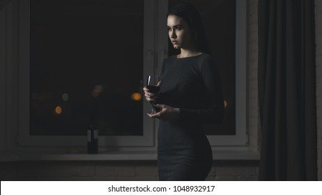 Silhouette of woman at window with glass of wine at night, shallow depth of field