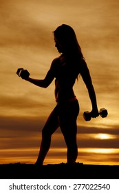 A silhouette of a woman working out with her weights.