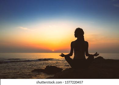 Silhouette of woman yoga in Lotus position on the shore of ocean at evening.