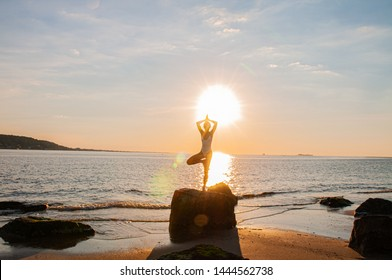Silhouette woman yoga on the beach at sunrise. Woman is practicing yoga at sunset on sea shore. Calm and self control.