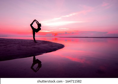 Silhouette woman with yoga posture on the beach at sunset with reflection.