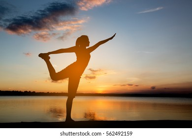 Silhouette woman with yoga posture  at sunset.
