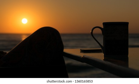 silhouette of a woman's foot drinking coffee in the open air at  seashoe