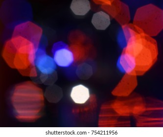 Silhouette of a woman's head surrounded by red, white and blue bokeh.