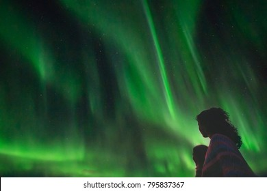 Silhouette of womans looking at the northern lights over drammen