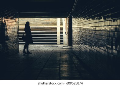 Silhouette of women against underground passage stairs leading up on the street