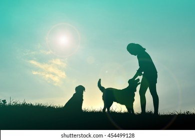 Silhouette women and dog playing at sunset