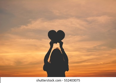Silhouette of women hands holding heart shape at the sky sunset background. concept love valentine day