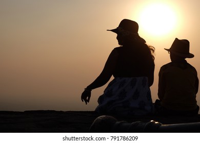 Silhouette of Women with her son sitting on a wall on fort, sunset