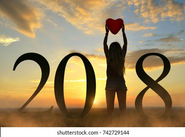 Silhouette of women holding balloon in heart shape in hands while celebrating New Year 2018.