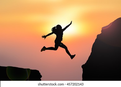 Silhouette women jumping on top mountain