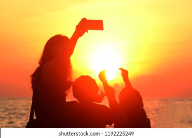 A silhouette of a women taking selfie photos with kids during sunset at the beach.
