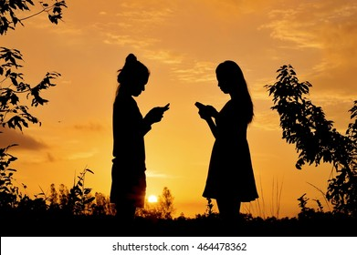 Silhouette of women using smart phones at sunset