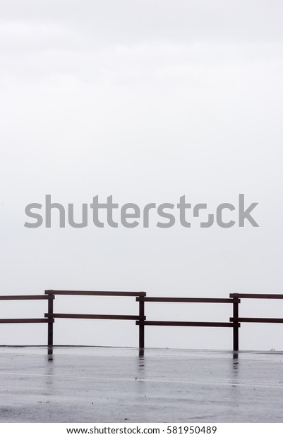 Silhouette of a wooden fence against a cloudy and foggy mountaintop sky, with a wet and reflective road. Minimalist travel backgrounds concept.