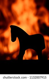 Silhouette of a wooden horse toy against a red, orange and yellow blazing fire in a house on fire. Burning home, arson, fire safety and danger theme.