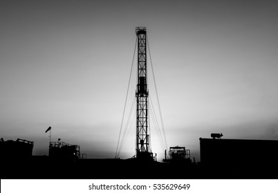 Silhouette of work over rig in oilfield at sunset  - black and white