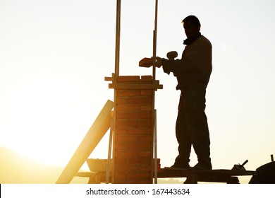 Silhouette of worker building a chimney on new house