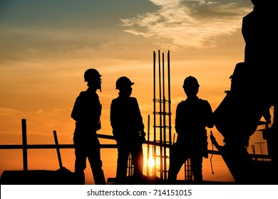 Silhouette worker civil engineer and safety officer in  industrial sector construction over blurred natural background sunset success team work business concept