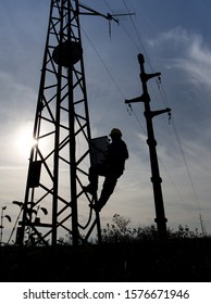 Silhouette of a worker climbing on a electrical lamppost