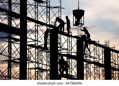 Silhouette of worker. Construction Building casting concrete work on scaffolding.