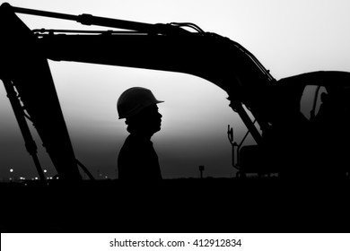 Silhouette of worker at construction site in oilfield. heavy equipment background - sunset -black and white