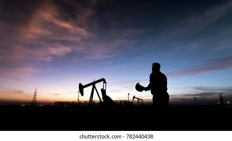 Silhouette of worker at crude oil pump in the oilfield at sunset.