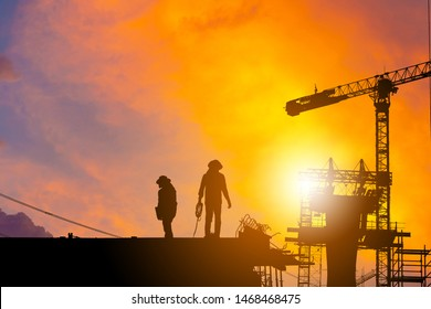 Silhouette of Worker on building construction site at sunset in evening time.