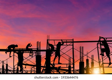 Silhouette of worker on building site, construction site at sunset in evening time.
