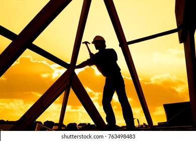 silhouette of worker roofer builder working on roof structure on construction site