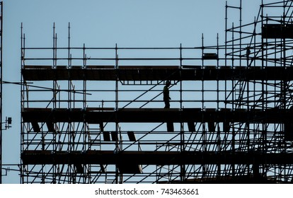silhouette of worker at scaffolding, working day at building construction, profile sunset light structure of scaffolding and cranes